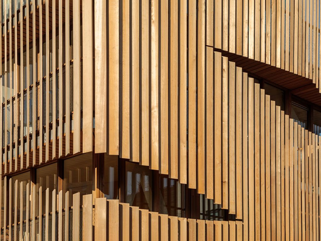 Freebooter: A slatted-wood facade enables optimal distribution of natural light while enhancing required levels of privacy. The building's hybrid structure, comprising CLT and steel, was prefabricated offsite, enabling a construction time of six months. . Image credit: Francisco Nogueira